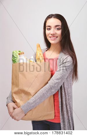 Young woman with paper bag of products on light background