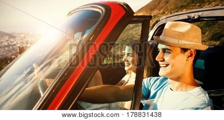 Side view of smiling couple on their way to beach in classy car