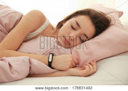 Young woman with sleep tracker resting in bed at home