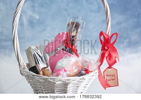 Easter basket with presents and greeting card on blue background