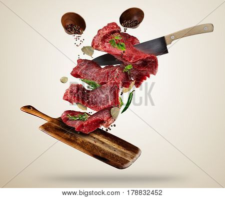 Flying pieces of raw steaks, with ingredients for cooking, served on wooden board. Knife cutting the meat. Concept of food preparation in low gravity mode. Separated on smooth background
