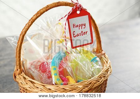 Easter basket with toy, cookies and greeting card, close up