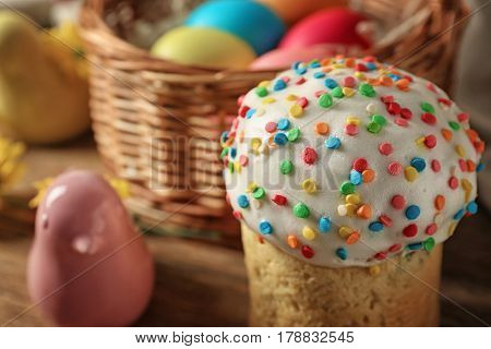 Easter cake with decorative bird and basket on wooden table