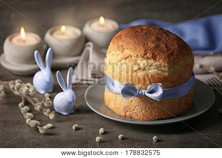 Composition of Easter cake on plate and rabbits on blurred background
