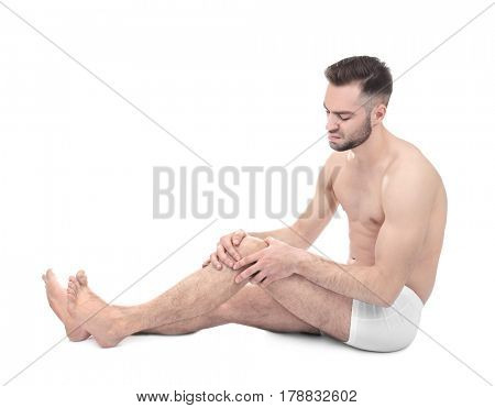 Young man suffering from pain in knee on white background