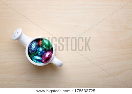 Decorative watering can full of chocolate eggs in colorful foil wrap on wooden table