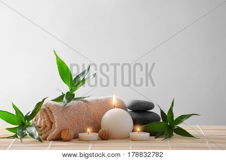 Spa stones, towel and candles on color background