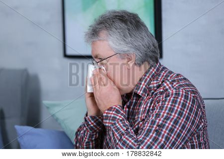 Senior man blowing nose on tissue at home