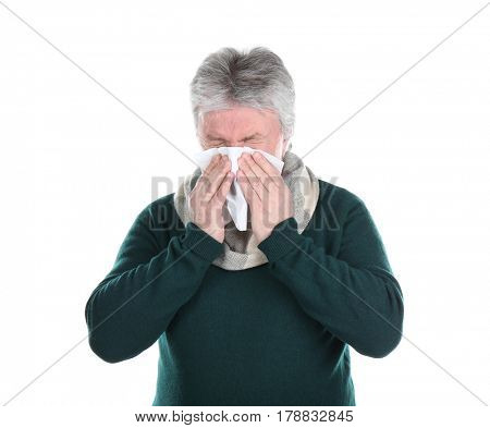 Senior man blowing nose on tissue against white background