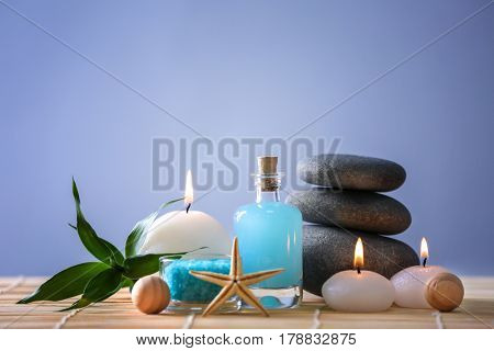 Spa stones with candles on color background