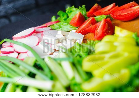 Wooden board with cut organic raw vegetables. Healthy food. Ingredients for salad or soup.