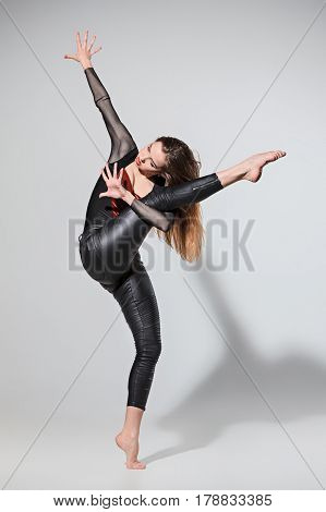 The woman dancing in contemporary stile of ballet at studio on gray