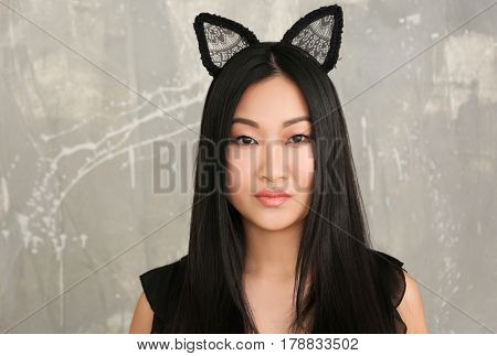 Young woman in cat ears on color background