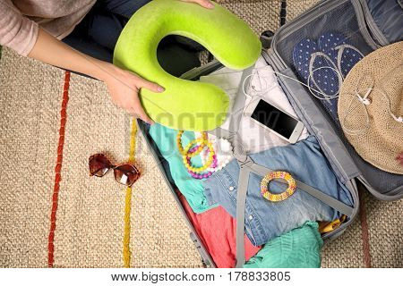 Woman with travel pillow packing suitcase at home