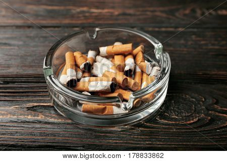 Glass ashtray with cigarette butts on wooden background