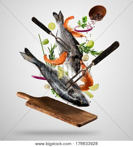Flying raw whole bream fish and prawns, with ingredients for cooking. Freeze motion. Fork holding the meat. Concept of food preparation in low gravity mode. Separated on smooth gray background