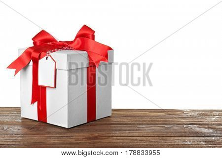 Beautiful gift box with red ribbon and blank label on wooden table