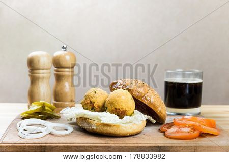 Vegan burger ingredients on wood table. Vegetables, vegan ball cutlets made of chick peas soft drink on cutting board ready to be put into vegetarian hamburger