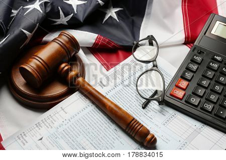 Judge gavel, calculator, eyeglasses and tax forms on American flag background