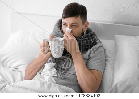 Young ill man drinking hot tea at home