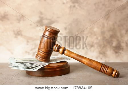 Judge gavel and money on table against color background