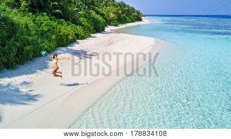 Beautiful young woman jumping on tropical beach on Maldives. Concept of freedom ,vacation, travel and beach holidays. Summer theme.