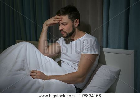 Handsome young man suffering from headache while resting in bed at night