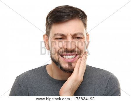 Handsome man suffering from toothache on white background