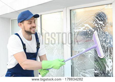 Young man washing window outdoors