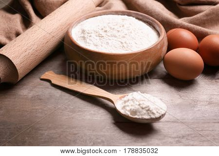 Bowl with flour, roller pin, eggs and spoon on wooden table