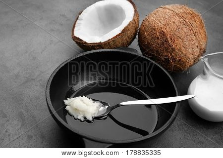 Spoon with coconut oil on frying pan
