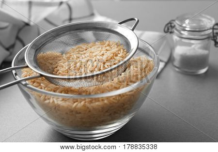 Sieve with raw brown rice in bowl on table