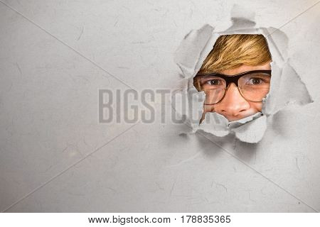 Happy blond hipster smiling against circle hole in paper 3d