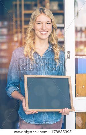 Portrait of smiling owner holding open signboard in supermarket