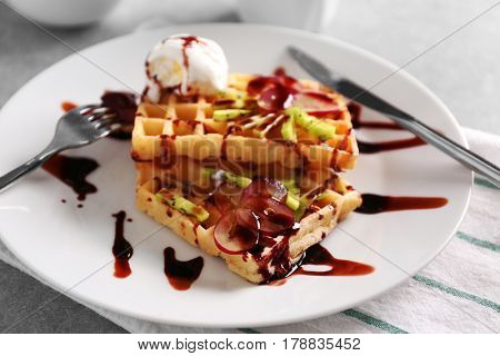 Delicious waffles with fruits, ice-cream and syrup on white plate