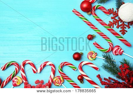 Christmas candy canes and decor on color wooden background