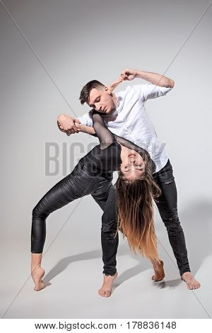 Two people dancing in contemporary stile of ballet at studio on gray