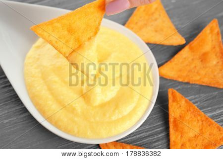 Dipping chips into bowl with cheese sauce on wooden table
