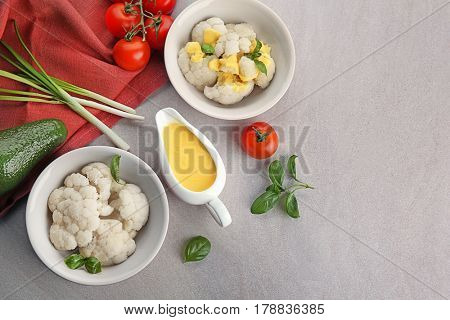 Bowls of delicious cauliflower, vegetables and cheese sauce in gravy boat on light background