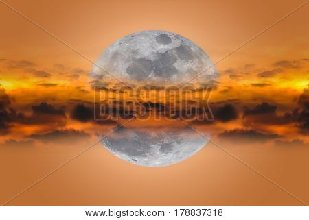Super moon between clouds on orange nature background. Night sky and silhouette of cloudy. The moon image NOT furnished by NASA.