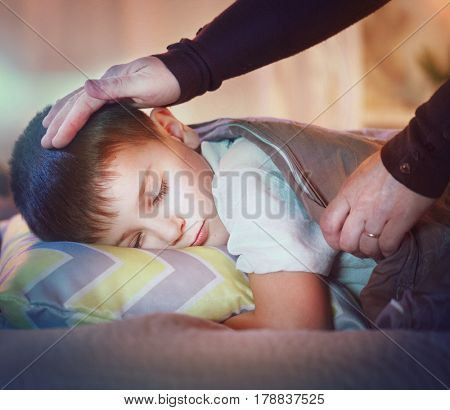 Child sleeping and dreaming in his bed, Mother cover her little son with a blanket. Mum touching the child on the head. Childhood and parenthood concept, warm and healthcare