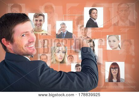 Businessman pointing with his finger against orange background