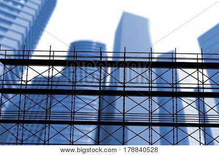 3d image of construction scaffolding against three dimensional image of tall buildings