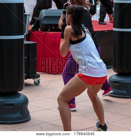 Young Girl with Shorts and White Tank Top: Fitness Boxing Workout with Punching Bag