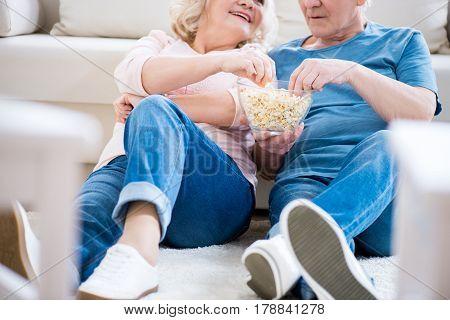 Cropped Shot Of Happy Senior Couple Eating Popcorn On Sofa