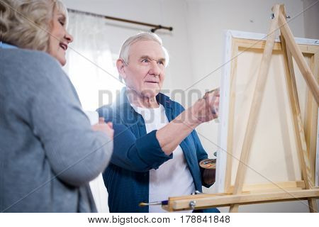 Happy Senior Couple Painting Picture On Easel At Home