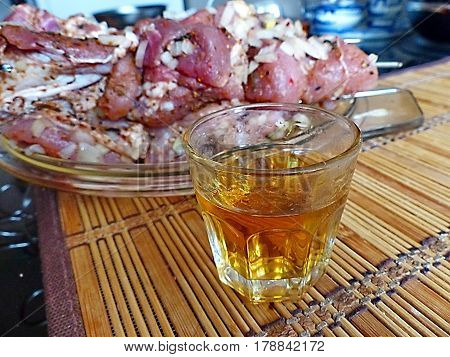 Close-up a glass of vodka on a background of raw shashlik. Natural products