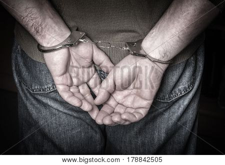 man hands in handcuffs close up background