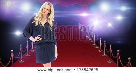 Serious gorgeous model wearing elegant dress posing against curtains of red color