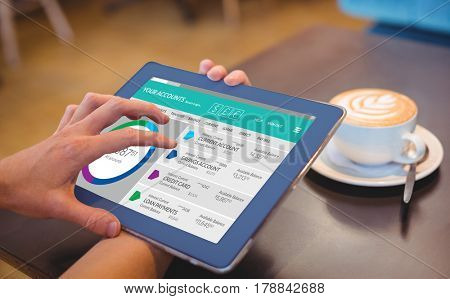Graphic image of bank account web site against close-up of digital tablet and coffee on table Close-up of digital tablet and coffee on table in the coffee shop